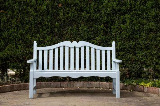 A white bench placed in front of a green hedge