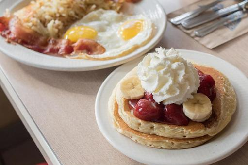 Breakfast of pancakes with plenty of whipped cream