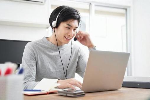 在宅でオンラインミーティングをする私服の日本人男性ビジネスマン