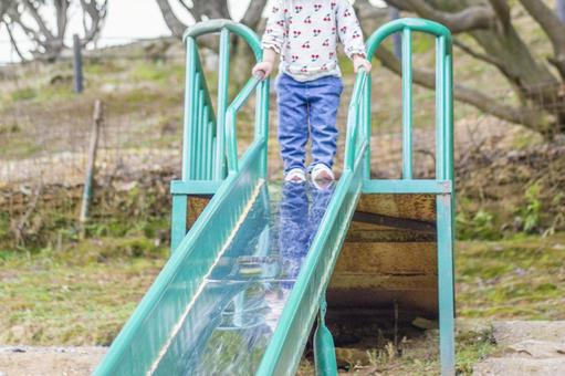 Toddler standing on the top of the slide