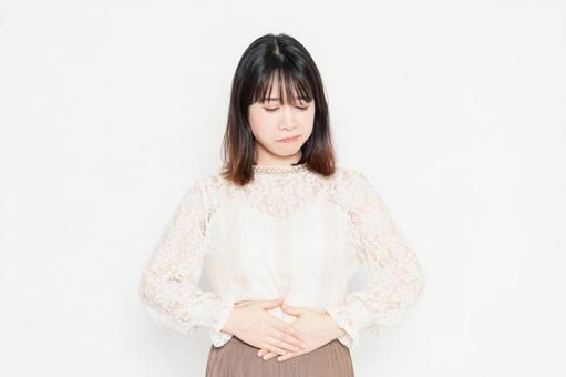 A young woman in a lace blouse standing in front of a white background and putting her hands on her belly