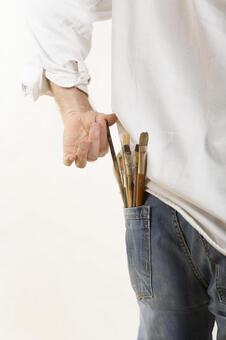 Person who removes paint brush from pocket