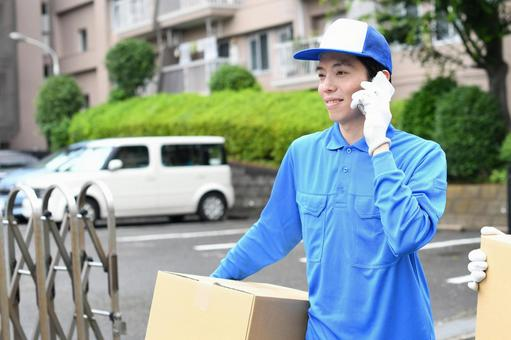 Image of a man wearing work clothes making a phone call while carrying a moving cardboard