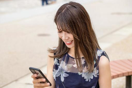 A smiling woman sitting on a park bench and looking at her smartphone