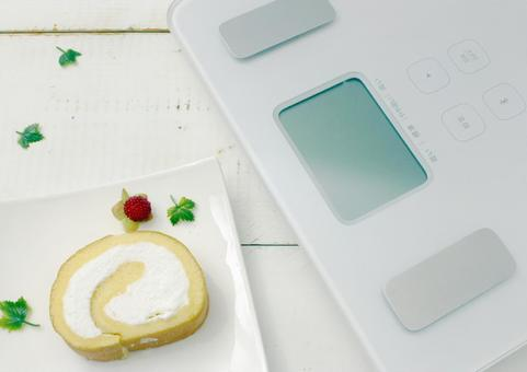Roll cake and diet letters and scales placed on a white wooden table