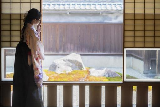 A woman in a hakama looking into the courtyard