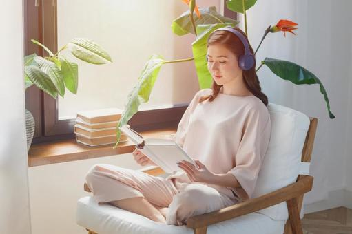 A woman listening to music while reading a book at home