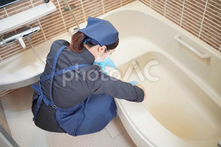 お風呂掃除をする家事代行の女性の写真
