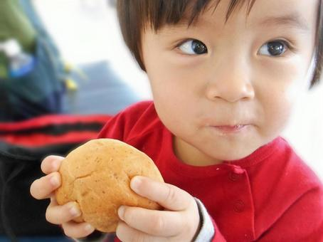 Baby eating bread and smiling