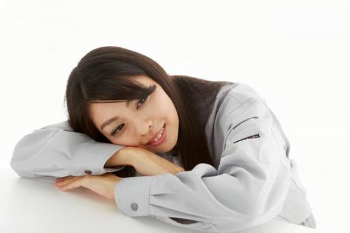 A young woman in work clothes staring at her face lying on her face 2