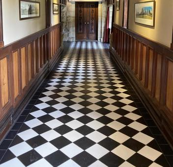 A checkered corridor with a mysterious atmosphere and a solid wooden door beyond it