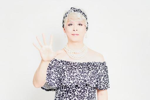 Drag queen standing in front of a white background and showing numbers with her fingers