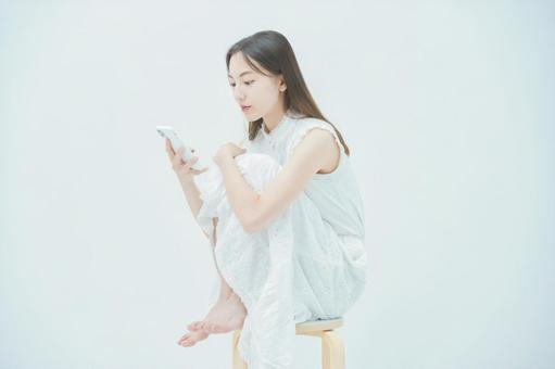 A woman looking at a smartphone with unpleasant feelings