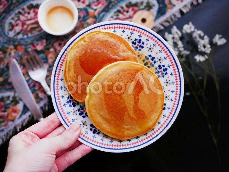 ホットケーキのお皿を手で持つの写真