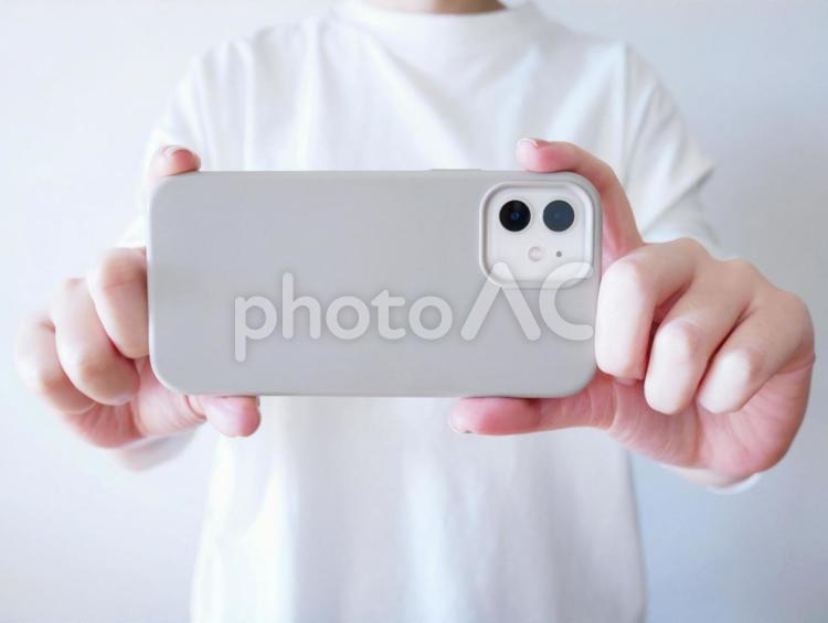 スマートフォンで写真を撮る女性の写真