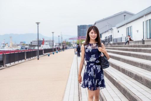 A smiling woman walking along the coastal promenade