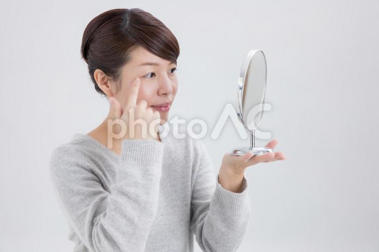 目尻を気にする女性(笑顔)の写真