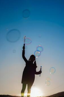 Silhouette of a girl playing soap bubbles