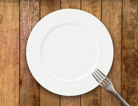 White dish and fork wood grain background
