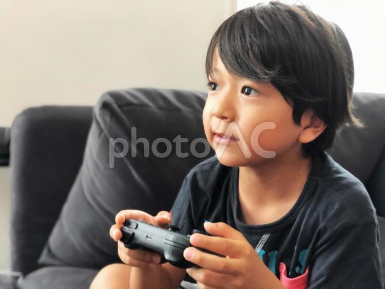 リビングでゲームをする少年の写真