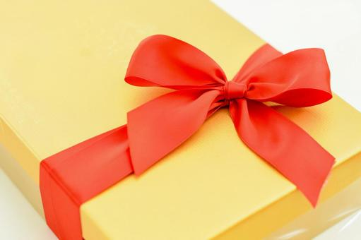 Gold box with a red ribbon