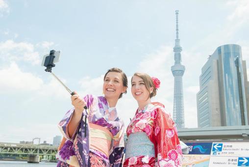 Yukata women taking self-shot at the river side Foreign tourists 3