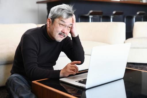 Elderly (senior) man worried in front of a computer