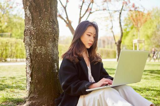 Asian woman 6 using a laptop under the tree