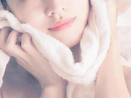 Woman wiping face with towel