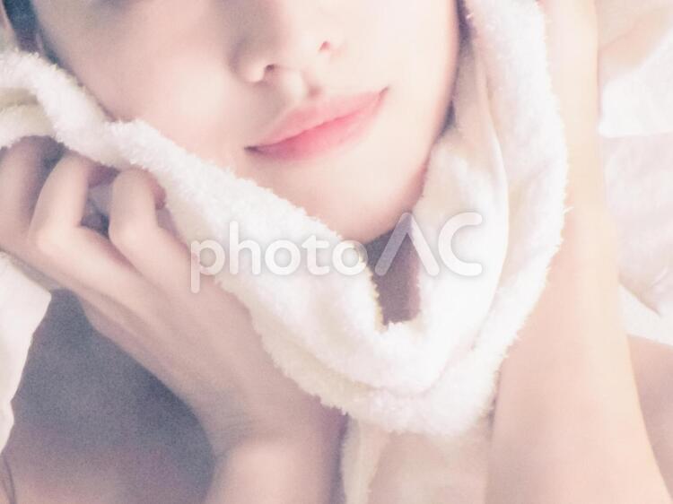 タオルで顔を拭く女性の写真
