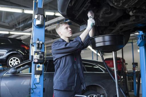 Automobile mechanic working under the car 11