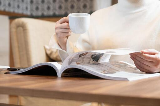 A woman's hand reading a fashion magazine with a coffee cup
