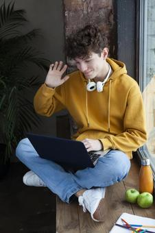 Teenage boy taking online lessons by the window