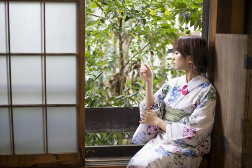 Yukata woman touching plants by the window