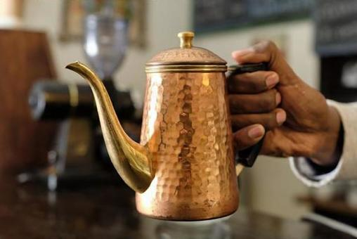 Ethiopian hands with a copper coffee pot