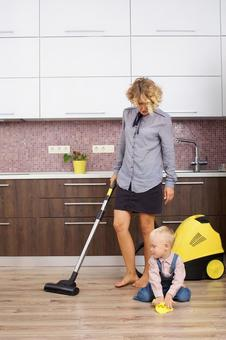 Working mother with a son and a vacuum cleaner that imitates cleaning 10