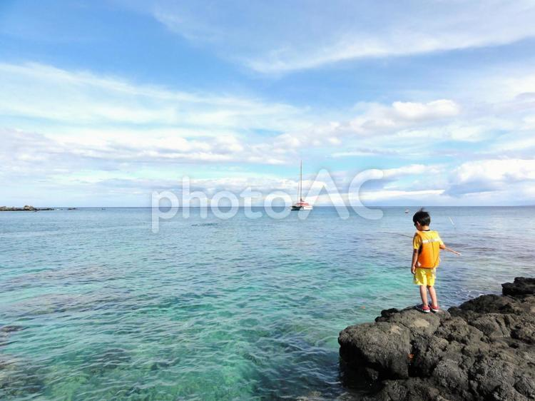 ハワイ島の海岸で釣りをする少年の写真