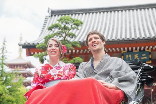 Foreign tourist couple in a yukata taking a rickshaw