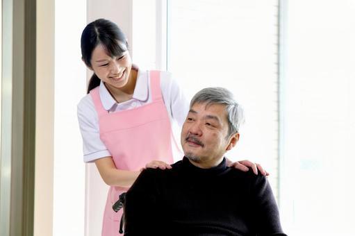 실내에서 이야기 휠체어를 누르면 젊은 여성과 시니어 남자