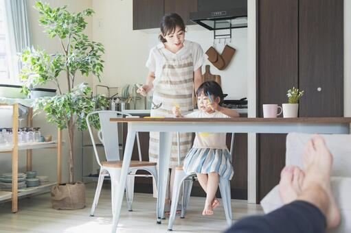 A girl drawing in the kitchen and a mother watching while cooking