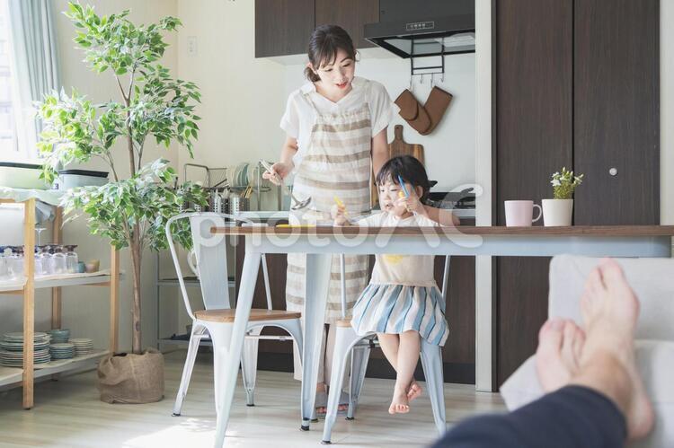 キッチンでお絵かきをする女の子と、料理をしながら見守る母親の写真