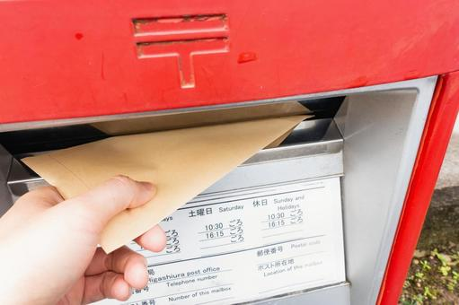 A photo of an envelope being posted to a mailbox. Image of mail.