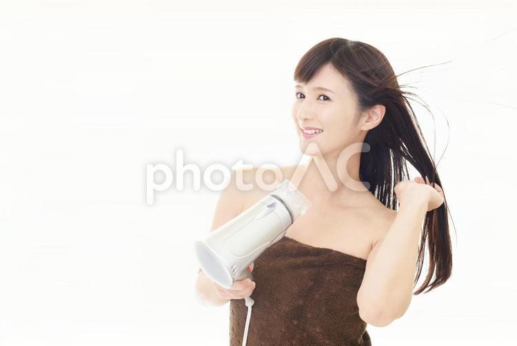 ドライヤーで髪を乾かしている女性の写真
