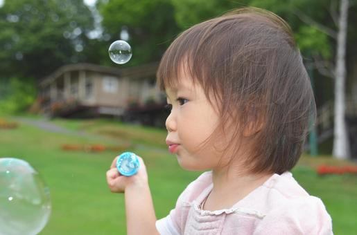 Girl playing soap bubbles (profile up)