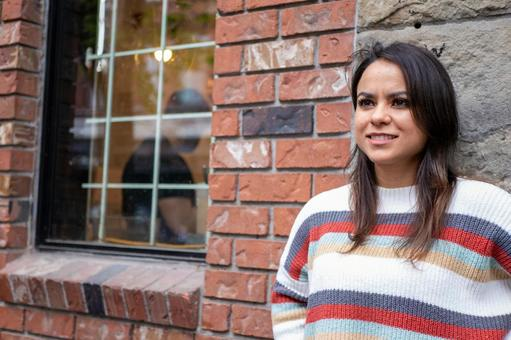 A portrait of a Mexican woman who decides coolly in front of a brick building
