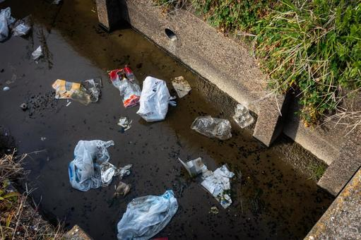 A photo of garbage dumped in an aqueduct taken in Japan. Image of environmental and social issues.