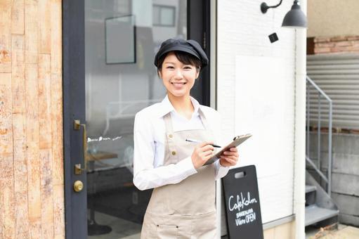 一位穿著圍裙在餐廳工作的女士在店內拿著一張紙條的照片