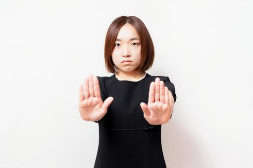 A woman in mourning dress standing in front of a white background and making an NG gesture