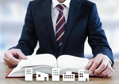 商人打開一本厚厚的書和建築輪廓