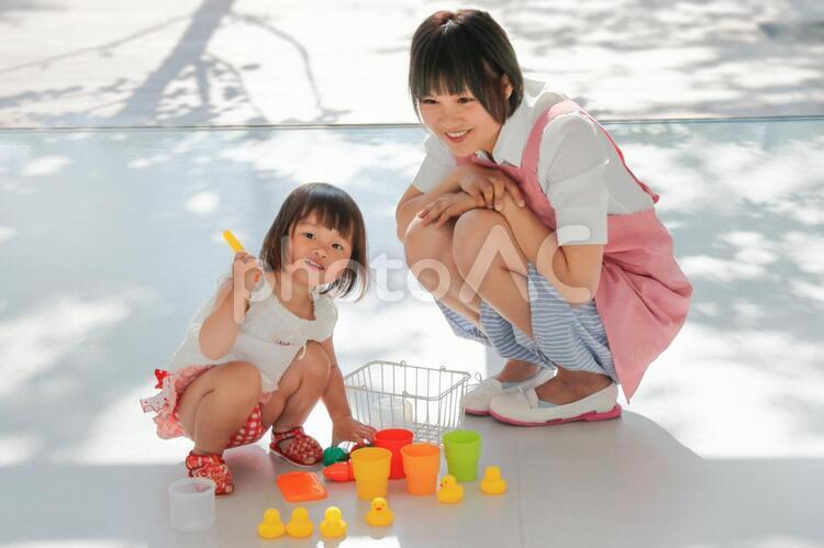 ままごとで遊ぶ子供とエプロン姿の女性の写真